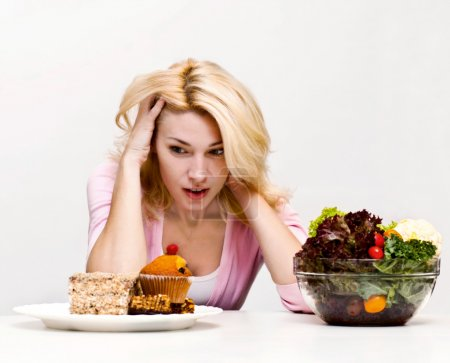 Photo for Young woman chooses between a salad and baking - Royalty Free Image