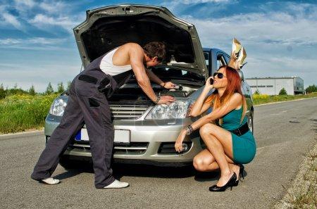 Mechanic fixing a car on a road