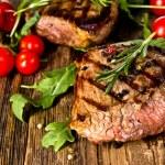 Grilled beef steaks on wood