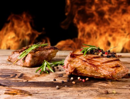 Photo for Grilled beef steaks with flames on background - Royalty Free Image