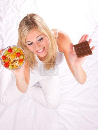 Photo pour Belle fille blonde ayant la décision quoi manger - repas sain ou malsain. axé sur les yeux - image libre de droit