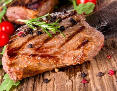 Foto de Delicioso bistec en tablones de madera - Imagen libre de derechos
