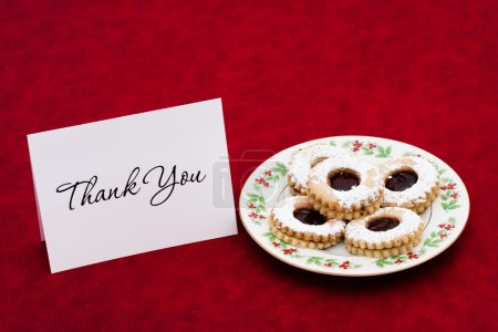 Photo for A plate of sugar cookies and a blank card on a red background - Royalty Free Image