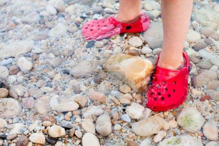 Photo pour Enfant debout en eau peu profonde avec de belles chaussures rouges - image libre de droit