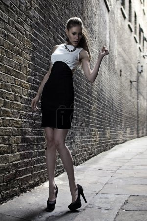 German blonde tall fashion model in a London Passing Alley posing wearing black white dress