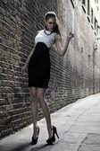"""Постер, картина, фотообои """"Немецкий блондинка Талль модель в Лондоне прохождения аллее позирует носить черное белое платье"""""""