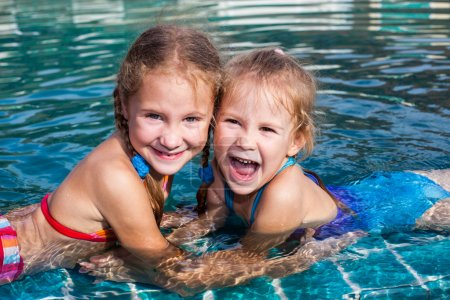 Two little girls playing in the pool