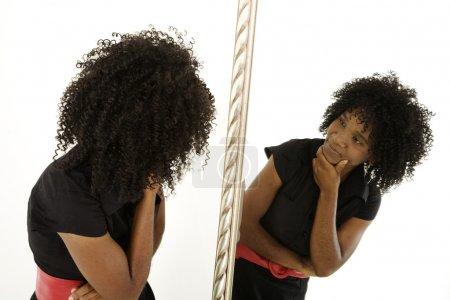 Photo pour Dame qui se regarde dans un miroir avec une expression quiz - image libre de droit