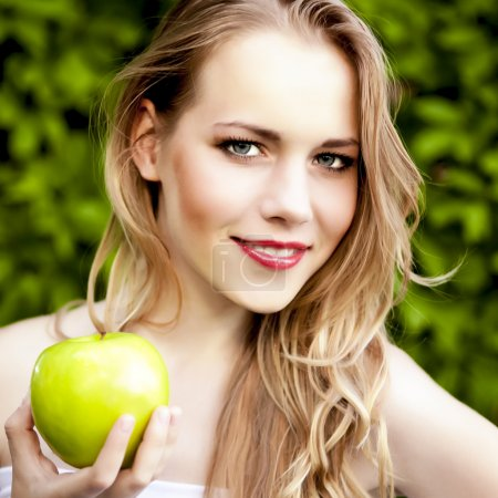 Portrait of a beautiful girl with an apple