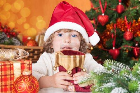 Photo pour Joyeux enfant tenant chaussette rouge contre l'arbre de Noël avec des décorations - image libre de droit