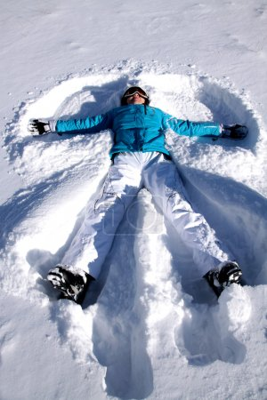 Photo for Young woman doing in the fresh snow angel - Royalty Free Image