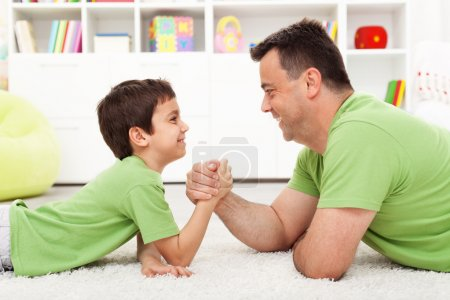 Photo for Father and son arm wrestling at home - childhood and parenting - Royalty Free Image