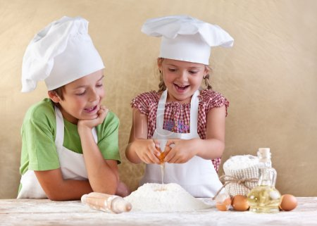 Photo for Kids preparing the dough for a cookie, pizza or pasta - having fun breaking the eggs - Royalty Free Image
