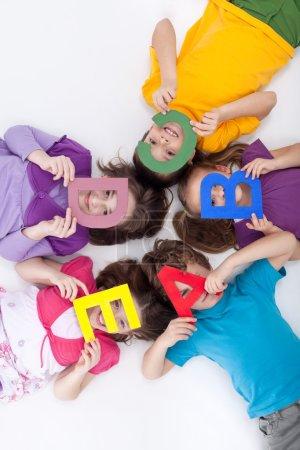 Photo pour Apprendre par le jeu concept - enfants avec de grandes lettres alphabétiques - image libre de droit