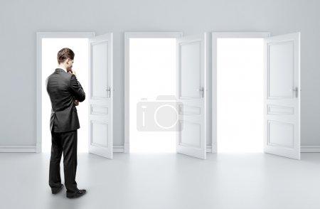 Man choosing of three opened doors