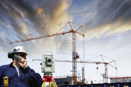 Photo pour Géodésie ingénieur avec l'industrie de la construction en arrière-plan, ciel ensoleillé - image libre de droit