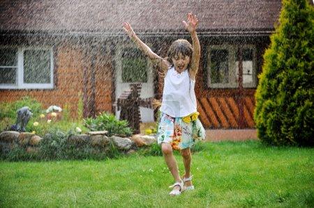 Little girl refreshing herself in a garden