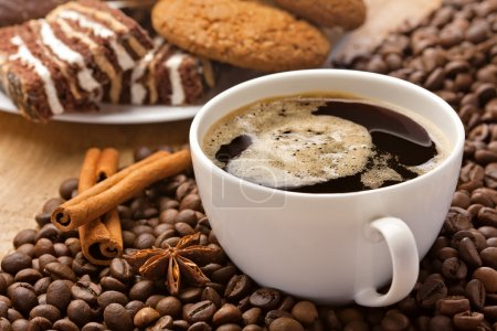 Coffee cup, sweets, cinnamon, anise on coffee beans