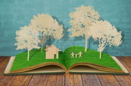 Photo pour Découpe de papier de symbole de la famille sur vieux livre d'herbe (Maison, Arbre, Maman, Papa, Enfant  ) - image libre de droit