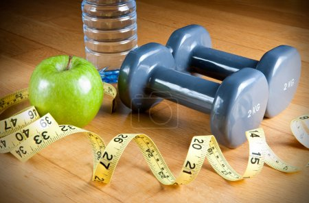 Photo for Pair of dumbbells, green apple, measuring tape and bottle of water. Exercise and healthy diet concept. - Royalty Free Image