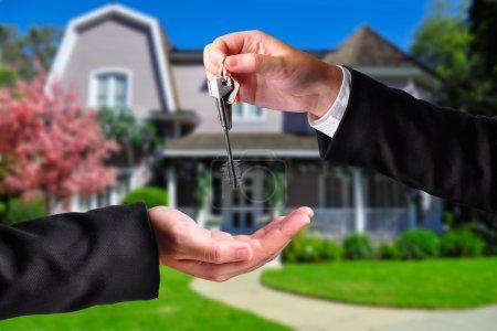 Photo pour Un coup de main de donner une clé à une autre main. les deux personnes en costume et une maison en arrière-plan. - image libre de droit