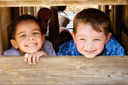 African-American child and caucasian child playing together on playground