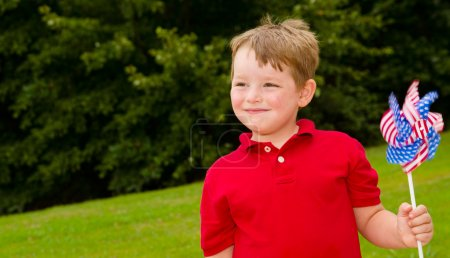 Child playing with American flag pinwheel to celebrate Independence Day on July Fourth with space for copy