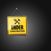 Under construction sign hanging with chain background