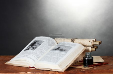 Old books, scrolls, ink pen and inkwell on wooden table on grey background