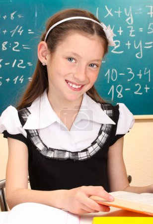 Beautiful little schoolgirl in classroom reading the book