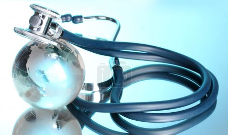 Globe and stethoscope on blue