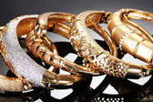 Beautiful golden bracelets on grey background