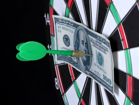 Dollar on bulls eye. Darts close-up on black background