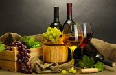 Barel, lahve a sklenice vína a zralé hrozny na dřevěný stůl na šedém pozadí