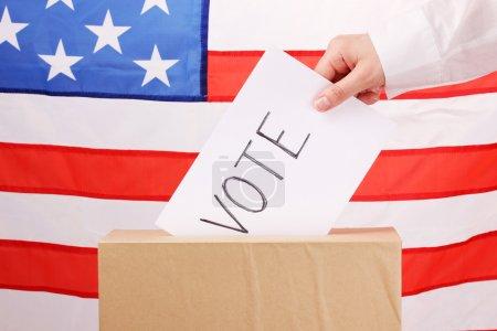Photo pour La main avec le vote au scrutin et la boîte sur le drapeau des usa - image libre de droit