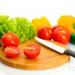 Fresh vegetables and knife on cutting board isolat...
