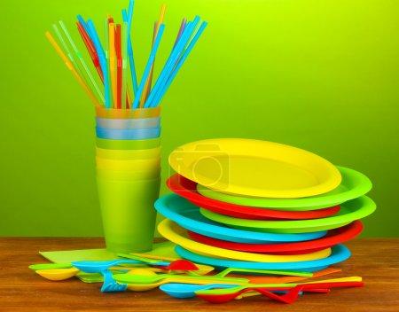Photo pour Lumineux vaisselle jetable en plastique sur une table en bois sur fond coloré - image libre de droit
