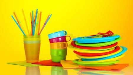 Photo pour Lumineux vaisselle jetable en plastique sur fond coloré - image libre de droit