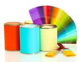 Plechovky s barvou, štětce a světlé paletu barev, izolované na bílém