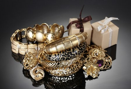 Beautiful golden jewelry and gifts on grey background