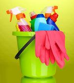 Kbelík s čištění předmětů na zeleném pozadí