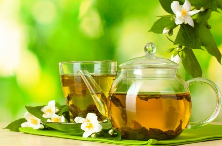Green tea with jasmine in cup and teapot on wooden table on green background