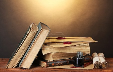 Photo for Old books, scrolls, ink pen and inkwell on wooden table on brown background - Royalty Free Image