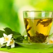 Cup of green tea with jasmine flowers on wooden ta...