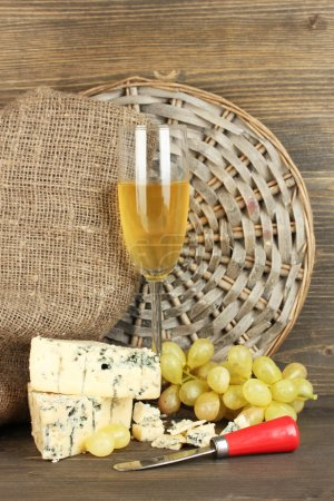 Composition of blue cheese and a glass of wine with grapes on wooden background close-up