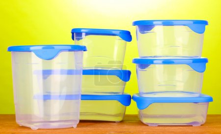 Photo for Plastic containers for food on wooden table on green background - Royalty Free Image