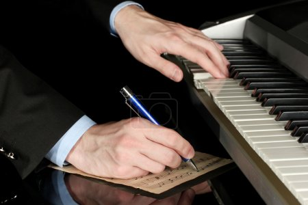 Man hands playing piano and writes on parer for notes