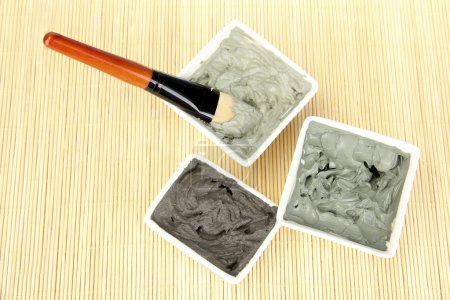 Cosmetic clay for spa treatments on straw background close-up