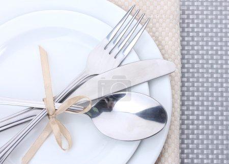 Photo pour Blancs assiettes vides avec la fourchette, cuillère et couteau attaché avec un ruban sur une nappe grise - image libre de droit