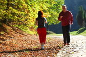 Woman and man walking cross country trail in autumn forest
